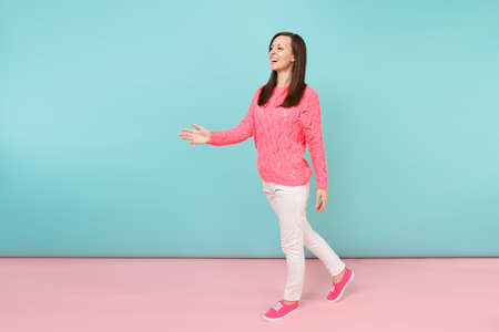 Full length portrait of smiling young woman in knitted rose sweater, white pants posing isolated on bright pink blue pastel wall background in studio. Fashion lifestyle concept. Mock up copy space 版權商用圖片