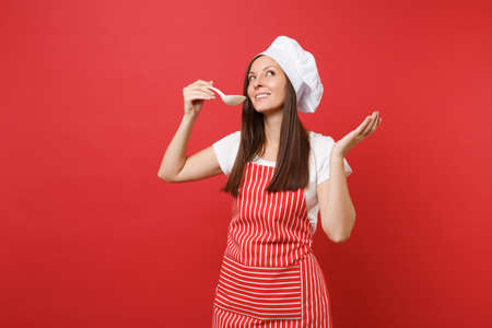 Housewife female chef cook or baker in striped apron, white t-shirt, toque chefs hat isolated on red wall background. Housekeeper woman hold tasting with soup ladle dipper. Mock up copy space concept