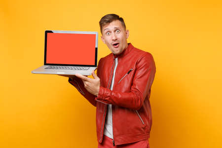 Portrait vogue fun young man in red leather jacket, t-shirt hold laptop computer blank empty screen isolated on bright yellow background. People sincere emotions lifestyle concept. Advertising area 免版税图像