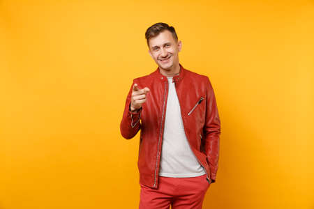 Portrait vogue smiling handsome young man 25-30 years in red leather jacket, t-shirt standing isolated on bright trending yellow background. People sincere emotions lifestyle concept. Advertising area