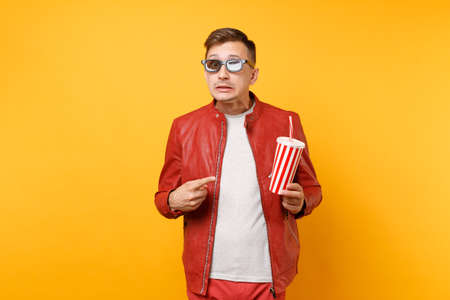 Portrait of vogue young man in 3d glasses, red leather jacket, t-shirt watching movie film, holding cup of soda or cola isolated on bright yellow background. People sincere emotions lifestyle concept