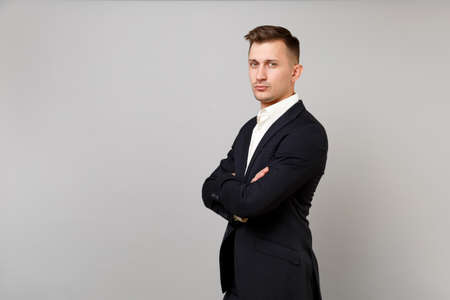 Portrait of handsome young business man in classic black suit and shirt holding hands folded isolated on grey wall background in studio. Achievement career wealth business concept. Mock up copy space 版權商用圖片