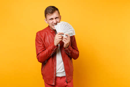 Portrait vogue fun mad young man in red leather jacket, t-shirt holding lots of dollars banknotes, cash money isolated on bright trending yellow background. People lifestyle concept. Advertising area