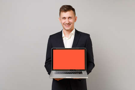 Smiling young business man in classic black suit, shirt holding laptop pc computer with blank empty screen isolated on grey background. Achievement career wealth business concept. Mock up copy space