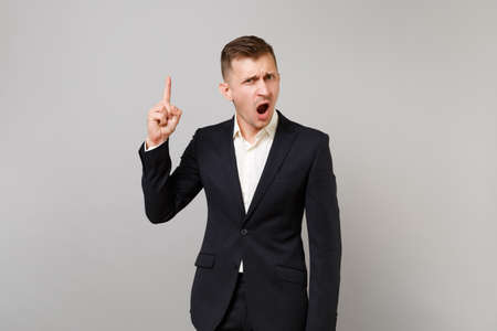 Outraged young business man in classic black suit, shirt swearing, pointing index finger up isolated on grey wall background in studio. Achievement career wealth business concept. Mock up copy space 스톡 콘텐츠