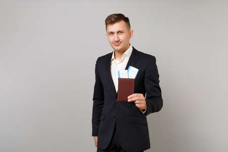 Handsome young business man in classic black suit, shirt hold passport, boarding pass ticket isolated on grey wall background in studio. Achievement career wealth business concept. Mock up copy space