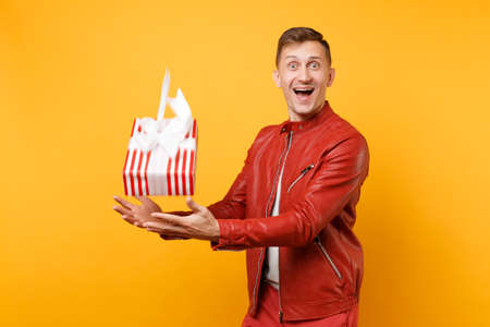 Portrait vogue smiling handsome young man in red jacket, t-shirt hold present box with gift isolated on bright trending yellow background. People sincere emotions lifestyle concept. Advertising area