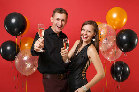Stunning young couple in black clothes celebrating birthday holiday party isolated on bright red background air balloons. St. Valentine's International Women's Day Happy New Year 2019 concept. 免版税图像