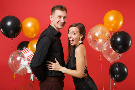 Young couple in black clothes hold gift box celebrating birthday holiday party isolated on bright red background air balloons St. Valentine International Women Day Happy New Year 2019 concept.