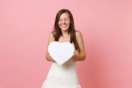 Cheerful bride woman with closed eyes in beautiful white wedding dress standing holding white heart with copy space isolated on pastel pink background. Wedding celebration concept. Advertising area