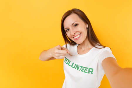 Selfie image of happy smiling satisfied woman in white t-shirt with written inscription green title volunteer isolated on yellow background. Voluntary free assistance help, charity grace work concept
