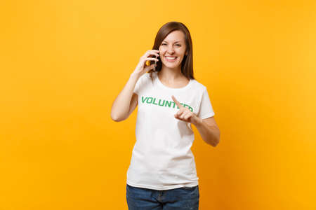 Young woman portrait in white t-shirt with written inscription green title volunteer talking on mobile phone isolated on yellow background. Voluntary free assistance help, charity grace work concept