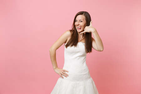 Funny bride woman in wedding dress doing phone gesture like says: call me back with hand and fingers like talking on telephone isolated on pink background. Communicating. Wedding concept. Copy space