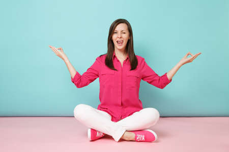Full length portrait of smiling young woman in rose shirt blouse, white pants sitting on floor isolated on bright pink blue pastel wall background studio. Fashion lifestyle concept Mock up copy space