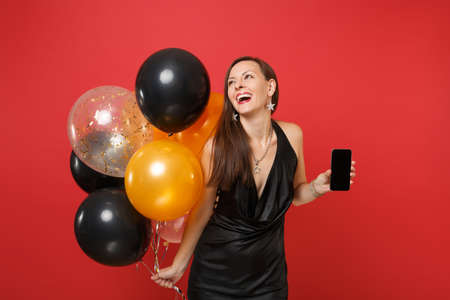 Laughing girl in black dress celebrating, looking up, holding mobile phone with blank black empty screen, air balloons isolated on red background. Happy New Year birthday mockup holiday party concept