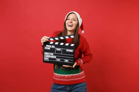 Laughing young Santa girl in Christmas hat holding classic black film making clapperboard isolated on bright red background. Happy New Year 2019 celebration holiday party concept. Mock up copy space Stock Photo