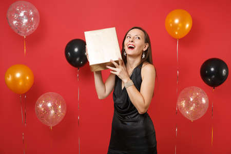 Happy young girl in little black dress celebrating holding golden box with gift present on bright red background air balloons. St. Valentine's Day Happy New Year birthday mockup holiday party concept
