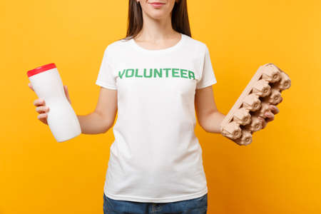 Woman portrait in white t-shirt with written inscription green title volunteer hold plastic bottle, cardboard box isolated on yellow background. Voluntary free assistance help, trash sorting concept