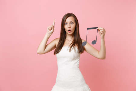 Shocked bride woman in wedding dress pointing index finger up hold musical note choosing staff musicians or DJ isolated on pink background. Wedding to do list. Organization of celebration. Copy space