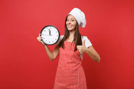 Housewife female chef cook or baker in striped apron, white t-shirt, toque chefs hat isolated on red wall background. Smiling woman holding in hand round clock hurry up. Mock up copy space concept
