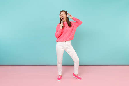 Full length portrait fun woman in knitted sweater, white pants, headphones sing song in microphone isolated on bright pink blue pastel wall background in studio. Lifestyle concept. Mock up copy space Banque d'images