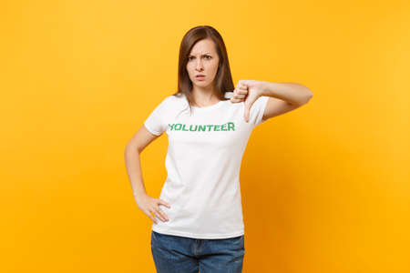 Portrait of sad upset shocked young woman in white t-shirt with written inscription green title volunteer isolated on yellow background. Voluntary free assistance help, charity grace work concept Stock fotó