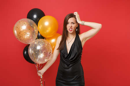 Concerned upset young woman in black dress putting hand on head holding air balloons while celebrating isolated on red background. Valentine's Day Happy New Year birthday mockup holiday party concept Stock Photo