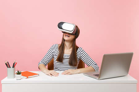 Young smiling woman in casual clothes, headset of virtual reality on head sit and work at white desk with pc laptop isolated on pastel pink background. Achievement business career concept. Copy space