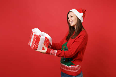 Side view of attractive pleasant young Santa girl giving or receiving red box with gift, present isolated on red background. Happy New Year 2019 celebration holiday party concept. Mock up copy space