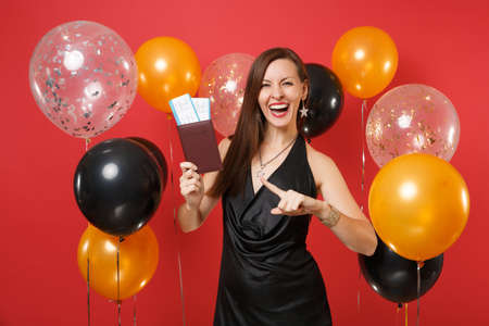 Laughing girl in black dress celebrating, pointing index finger on passport, boarding pass tickets in hand on bright red background air balloons. Happy New Year, birthday mockup holiday party concept Archivio Fotografico
