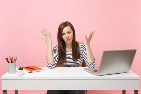 Dissatisfied upset tired woman in casual clothes spreading hand sit work at white desk with contemporary pc laptop isolated on pastel pink background. Achievement business career concept. Copy space