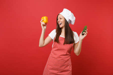 Housewife female chef cook or baker in striped apron, white t-shirt, toque chefs hat isolated on red wall background in studio. Woman hold yellow pepper, green cucumber. Mock up copy space concept Stock Photo