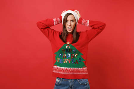 Bewildered upset young Santa girl in knitted sweater, Christmas hat clinging to head isolated on bright red wall background. Happy New Year 2019 celebration holiday party concept. Mock up copy space