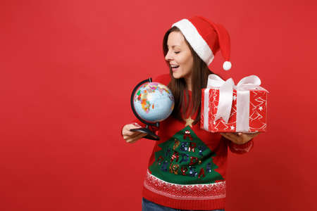 Pretty young Santa girl in Christmas hat looking on world globe holding red box with gift present isolated on red background. Happy New Year 2019 celebration holiday party concept. Mock up copy space Foto de archivo