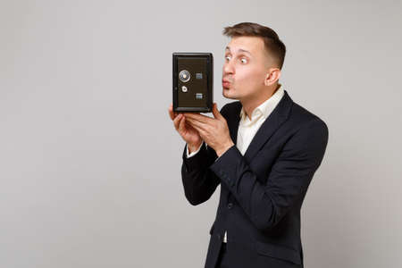 Funny young business man in suit blowing sending air kiss to metal bank safe for money accumulation in hand isolated on grey background. Achievement career wealth business concept. Mock up copy space