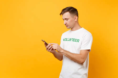 Young man portrait in white t-shirt with written inscription green title volunteer messaging on mobile phone isolated on yellow background. Voluntary free assistance help, charity grace work concept