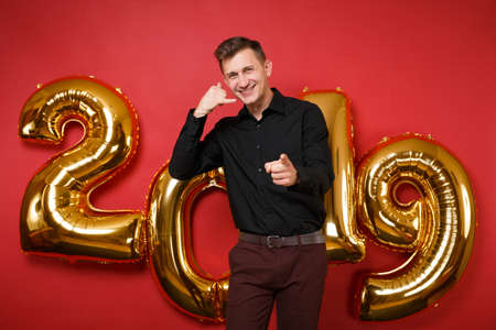 Merry handsome young man in black shirt celebrating holiday party standing isolated on bright red wall background, golden numbers air balloons studio portrait. Happy New Year 2019 Christmas concept