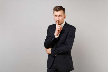 Serious young business man in classic black suit shirt say hush be quiet with finger on lips, shhh gesture isolated on grey background. Achievement career wealth business concept. Mock up copy space