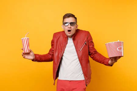 Portrait vogue young man in 3d glasses, leather jacket, t-shirt watching movie film, holding popcorn, cup of soda isolated on bright yellow background. People sincere emotions lifestyle concept.