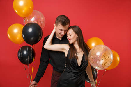 Stunning young couple in black clothes celebrating birthday holiday party isolated on bright red background air balloons. St. Valentine's International Women's Day Happy New Year 2019 concept. Stock Photo