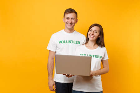Colleagues couple in white t-shirt with inscription green volunteer using typing laptop pc computer isolated on yellow background. Voluntary free work, assistance help, charity grace teamwork concept