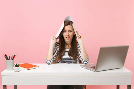 Young dissatisfied woman holding paper documents near head, working on project while sitting at office with laptop isolated on pastel pink background. Achievement business career concept. Copy space