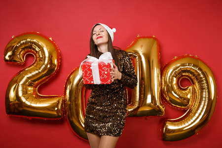 Merry Santa girl in shiny glitter dress, Christmas hat hold present box isolated on bright red wall background, golden numbers air balloons studio portrait. Happy New Year 2019 holiday party concept