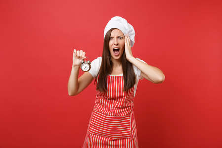 Housewife female chef cook or baker in striped apron, white t-shirt, toque chefs hat isolated on red wall background. Scared woman hold in hand retro alarm clock hurry up. Mock up copy space concept