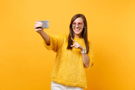 Smiling young woman in sweater, heart glasses doing taking selfie shot on mobile phone pointing index finger isolated on bright yellow background. People sincere emotions, lifestyle. Advertising area Banco de Imagens
