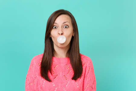 Amazed young woman in knitted pink sweater chewing blowing bubble gum balloon isolated on blue turquoise wall background studio portrait. People sincere emotions lifestyle concept. Mock up copy space Фото со стока