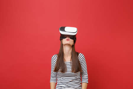 Portrait of young woman in casual striped clothes, virtual reality glasses standing, looking up isolated on bright red wall background. People sincere emotions, lifestyle concept. Mock up copy space