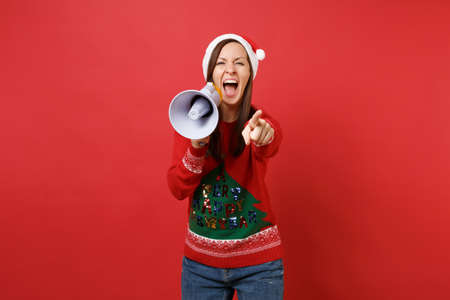Crazy young Santa girl in Christmas hat pointing index finger on camera, screaming on megaphone isolated on red background. Happy New Year 2019 celebration holiday party concept. Mock up copy space