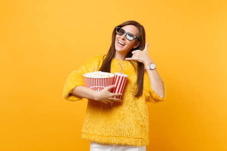 Woman in 3d imax glasses watching movie film in cinema holding popcorn cup of soda doing phone gesture like says: call me back with fingers like talking on the telephone isolated on yellow background