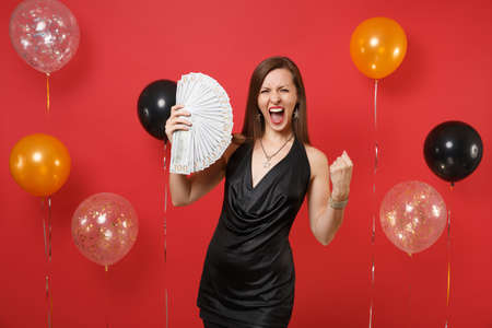 Crazy girl in black dress screaming, clenching fist like winner, holding bundle lots of dollars cash money on bright red background air balloons. Happy New Year, birthday mockup holiday party concept